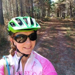 female mountain bike rider with pink jersey and green helmet smiling